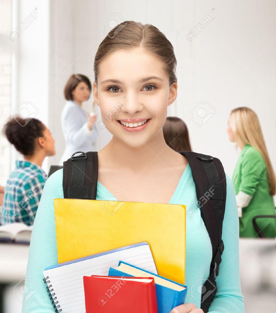 20772279-Chica-estudiante-feliz-con-mochila-y-cuadernos-en-la-escuela-Foto-de-archivo